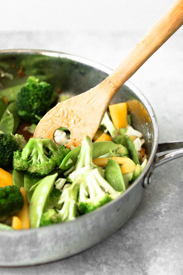 fresh broccoli, snow peas, and yellow peppers in a skillet