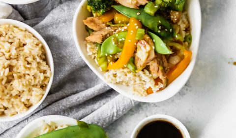 3 bowls of chicken stir-fry with one bowl of brown rice and a small bowl of sauce
