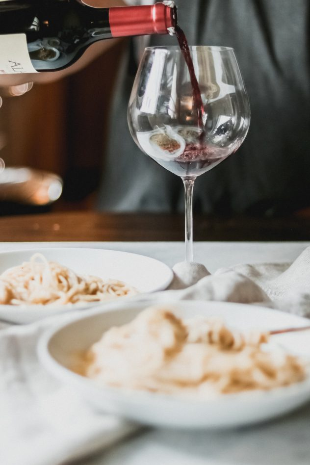 a person pouring red wine into a glass and two bowls of cacio e pepe sitting on the table