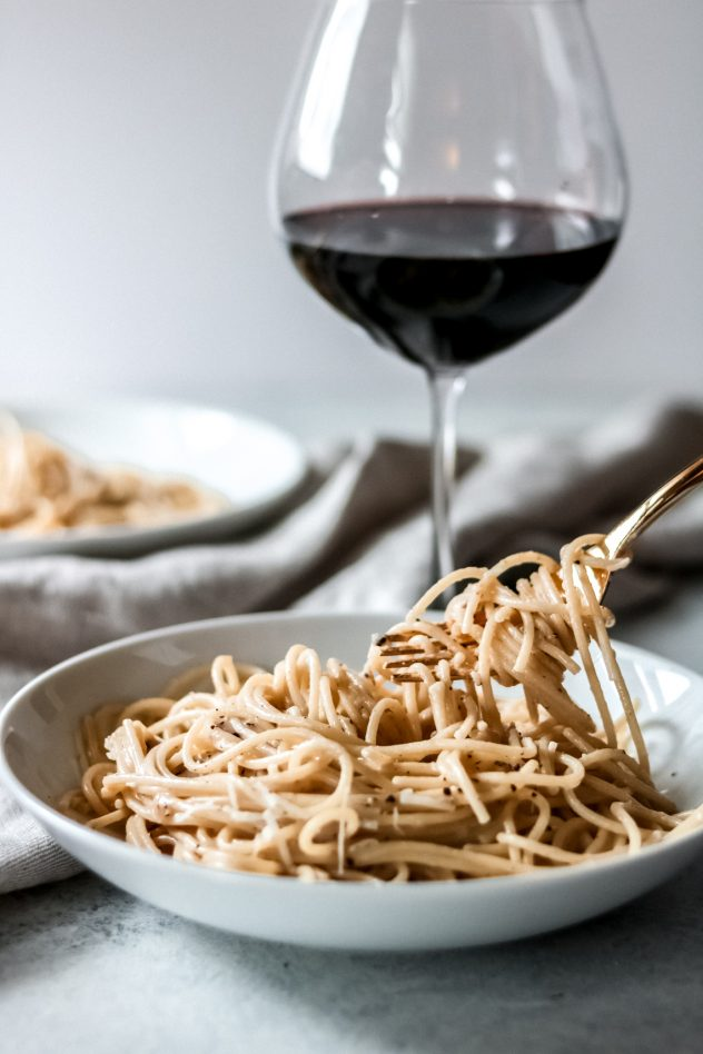 a fork twirling the cacio e pepe noodles and a glass of wine in the background