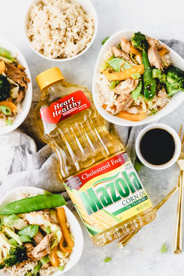 bottle of mazola corn oil with two bowls of chicken stir fry and a bowl of brown rice