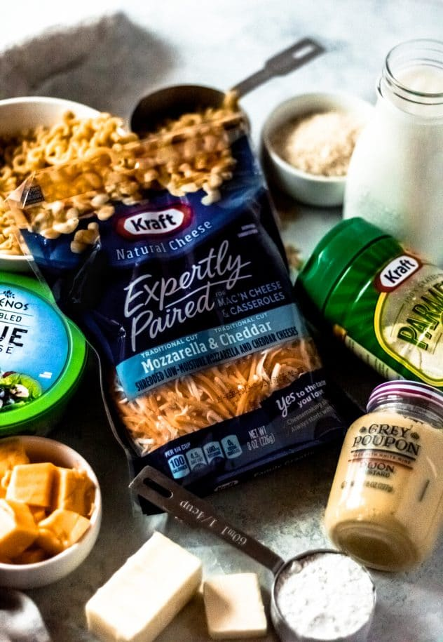 a gathering of all ingredients for the baked elbow macaroni and cheese recipe: KRAFT expertly paired for mac 'n cheese & casseroles, mozzarella & cheddar 8 oz package, elbow macaroni, milk, butter, flour, velveeta cheese cubes, blue cheese, parmesan cheese, grey poupon mustard and bread crumbs