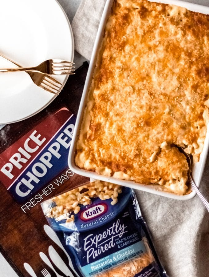 A 9x13 pan of baked elbow macaroni and cheese, a package of KRAFT expertly paired for Mac 'n Cheese & Casseroles, Mozzarella & Cheddar (8oz.), a price chopper shopping bag and two plates with two forks