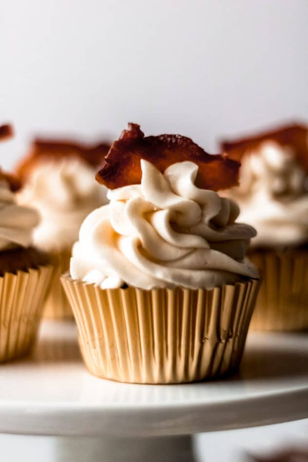 A close up shot of one maple bacon spice cupcake on a cupcake stand with additional cupcakes in the background