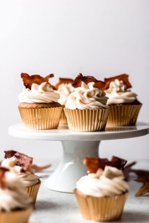 4 maple bacon spice cupcakes on a cake stand with additional cupcakes on the table surrounding the cake stand