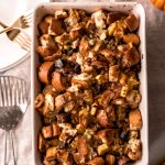 a 9x13 dish of sage, fig, and pancetta stuffing on a table with plates and forks and a serving spoon.