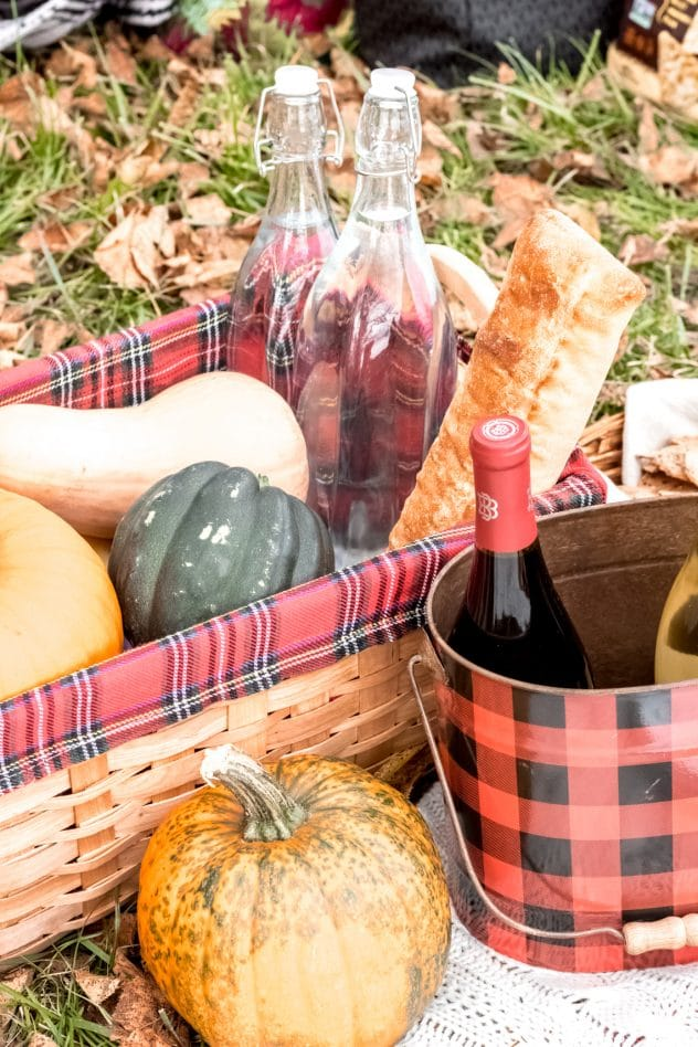 a basket with a variety of fall squash, a baguette, and bottles of water and wine