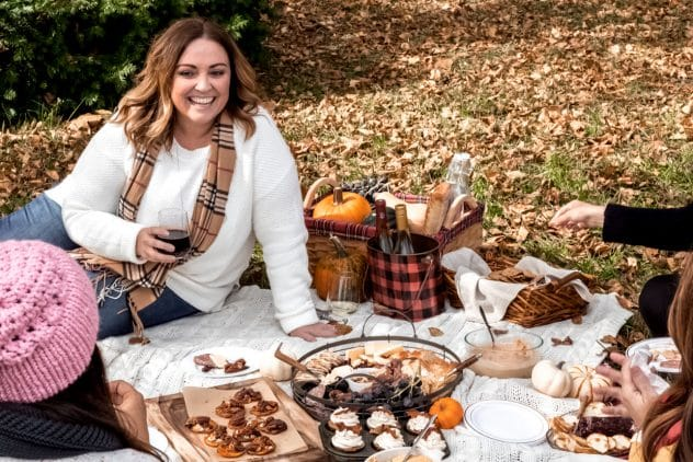 a woman enjoying a glass of wine at an outdoor friendsgiving picnic