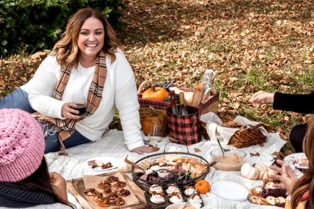 a woman enjoying a glass of wine at an outdoor friendsgiving picnic