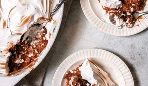 meringue-topped sweet potato casserole with two servings on a plate and a person holding a fork