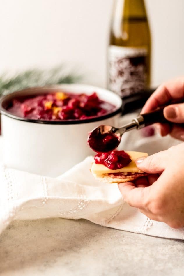 a woman spreading orange cranberry relish onto a slice of sharp cheddar cheese on top of a cracker. There is a saucepan of orange cranberry relish in the background with a bottle of Olive Tree cranberry pear balsamic vinegar