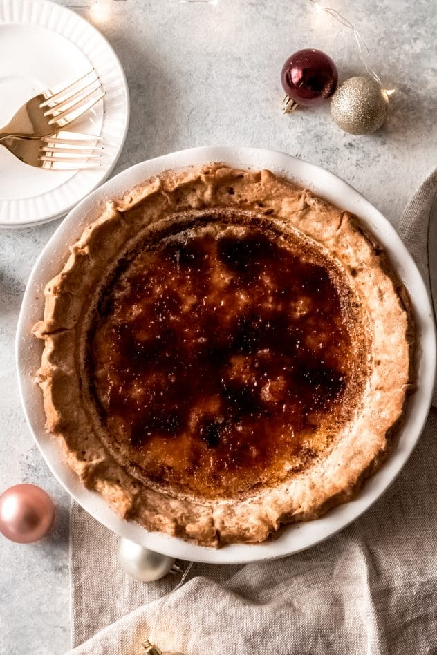 a bruleed eggnog custard pie in a white pie plate