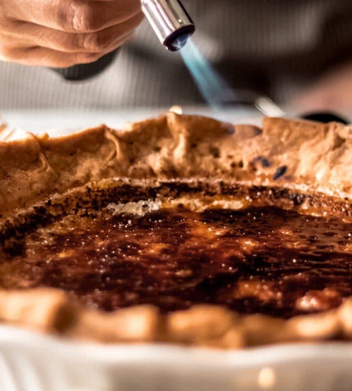 a woman using a kitchen torch on a bruleed eggnog custard pie