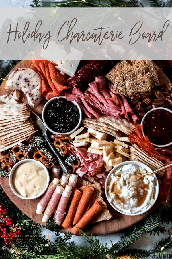 A round wooden holiday charcuterie board covered with various meats, cheese, crackers, and sweets, surrounded by holiday greenery