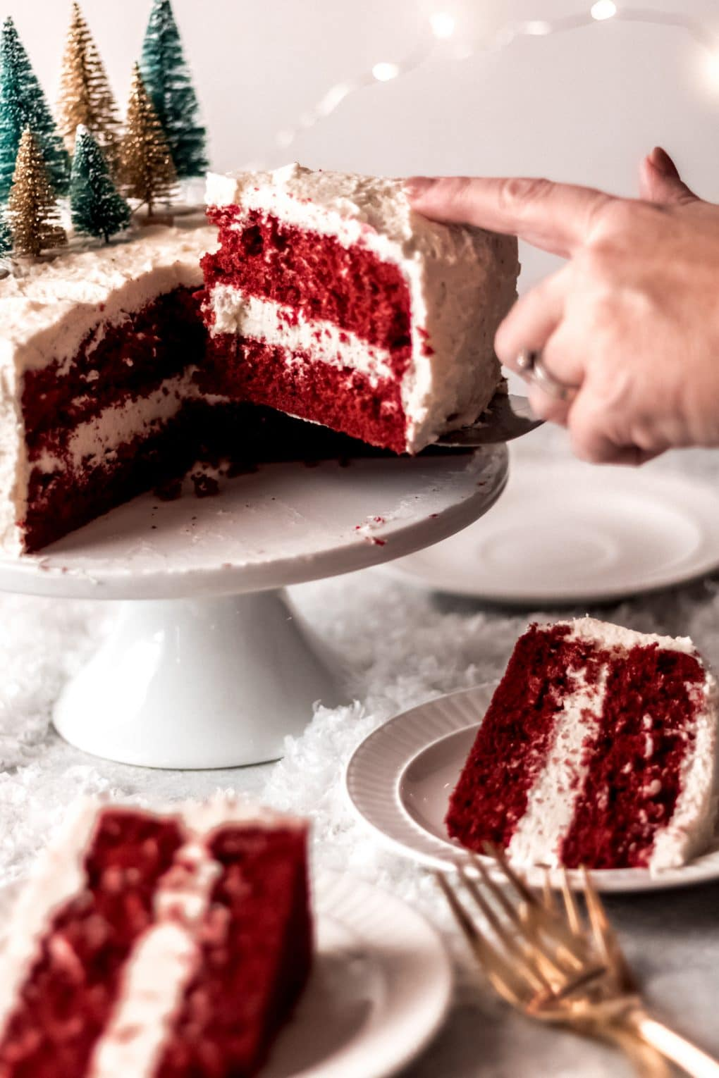 a woman pulling out a slice of red velvet cake with butter roux frosting getting ready to serve onto a plate. There are two other plates on the table that already have a slice of cake on them.