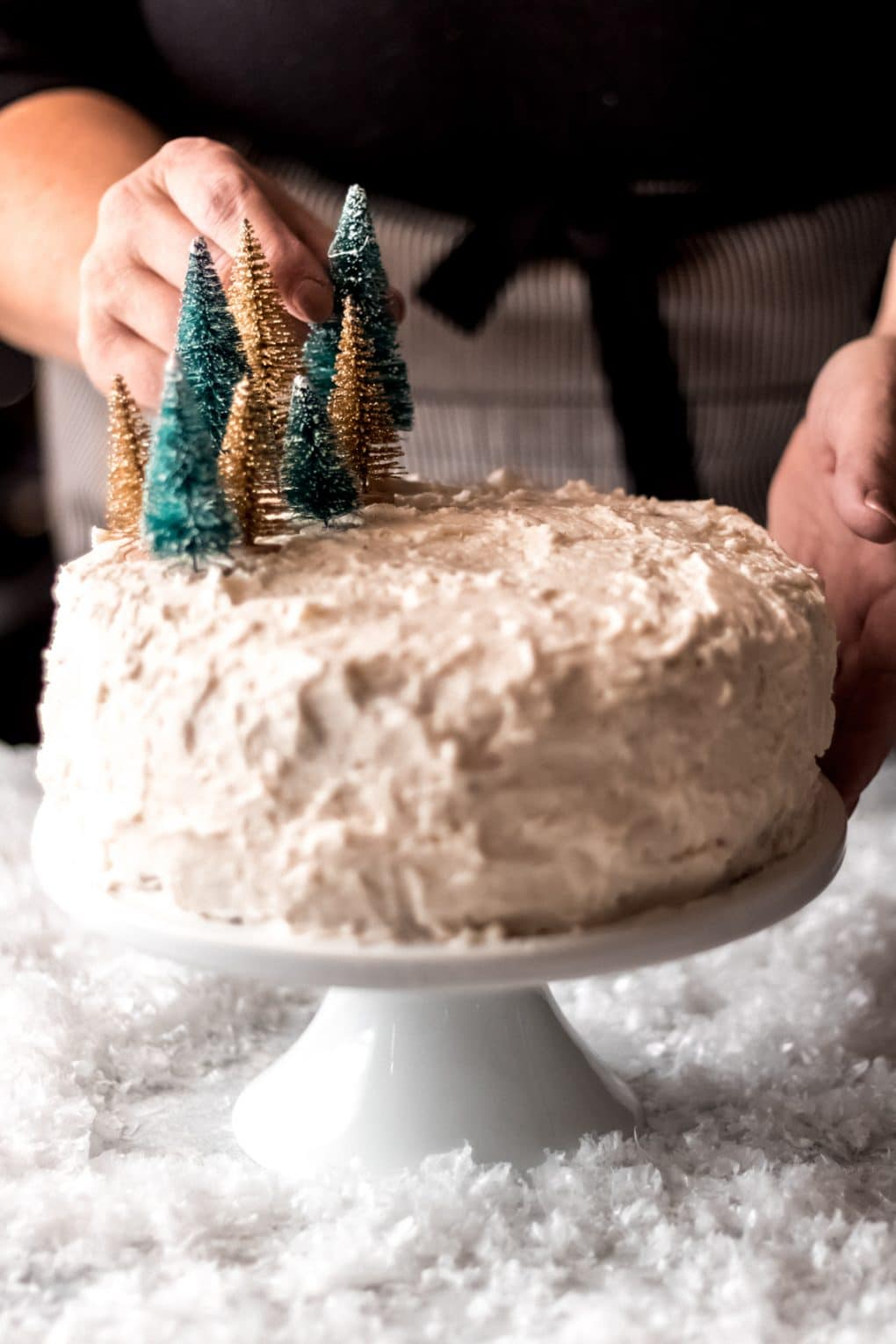 a woman adding miniature green and gold bottle brush trees to the top of a white icing cake on a white cake stand