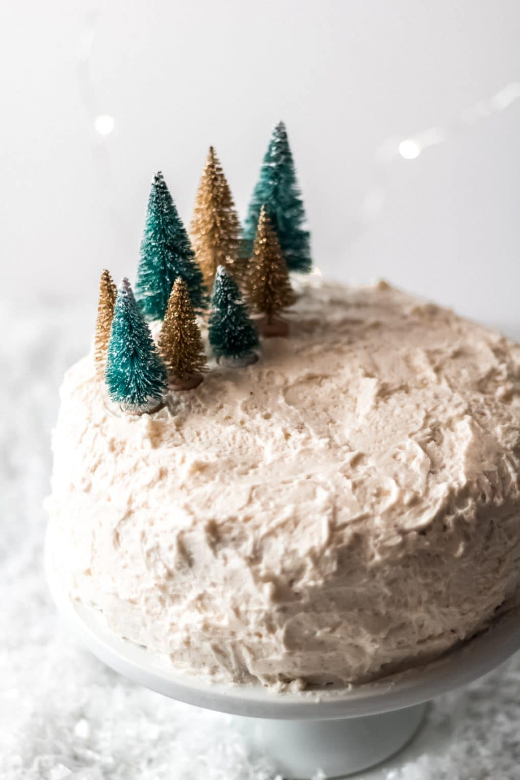 a red velvet cake covered with white butter roux icing on a white cake stand. It has miniature gold and green bottle brush trees grouped together on the left side of the cake.