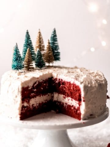 a red velvet cake on a white cake stand with miniature green and gold bottle brush trees