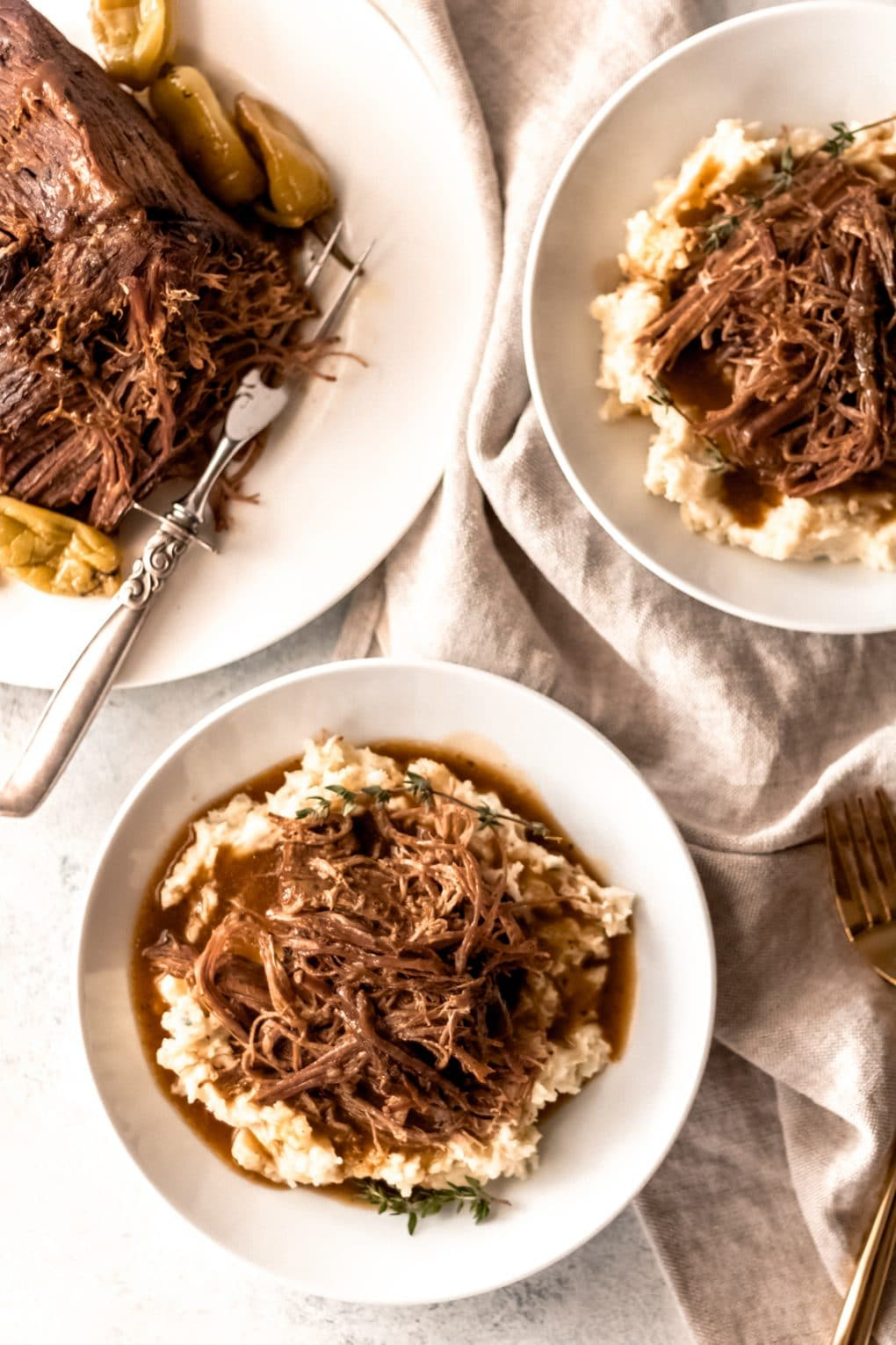 Two white bowls with mashed potatoes topped with shredded Mississippi pot roast. The Mississippi pot roast is on a white serving platter with a silver carving knife to the left of the bowls.