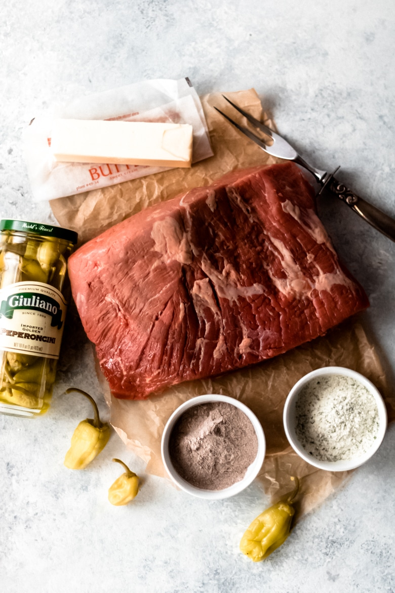 a Certified Angus Beef ® brand rump roast surrounded by the ingredients to make Mississippi Pot roast; stick of butter, jar of peperoncini peppers, au jus mix, and dry ranch mix