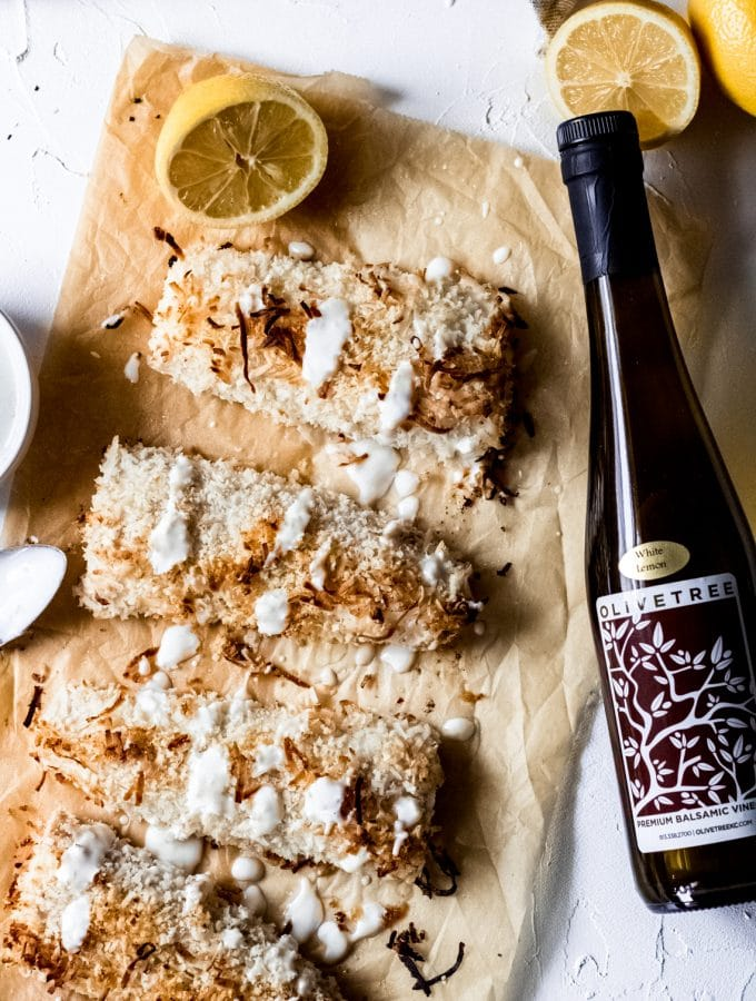 four coconut crusted Mahi-Mahi-Mahi fillets on a brown sheet of parchment paper. They have a creamy lemon sauce drizzled over the top of them and there's a bottle of Olive Tree's lemon balsamic vinaigrette laying next to them on the table.