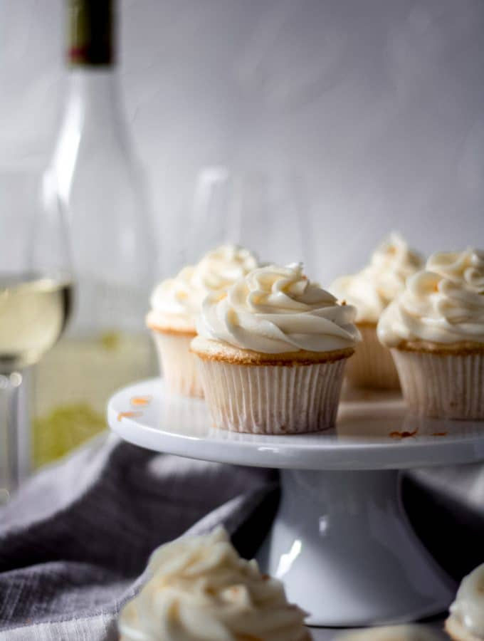 orange moscato cupcakes sitting on a white cake stand, there are also a few cupcakes sitting on the table. In the background there is a bottle of moscato and two wine glasses.