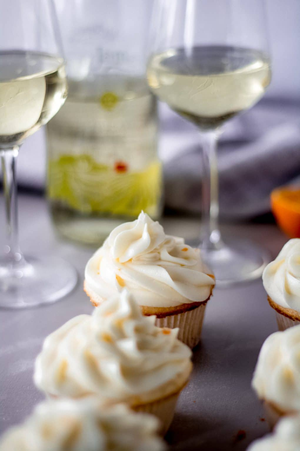 orange moscato cupcakes sitting on a table with a bottle of St. James Moscato in the background and two wine glasses.