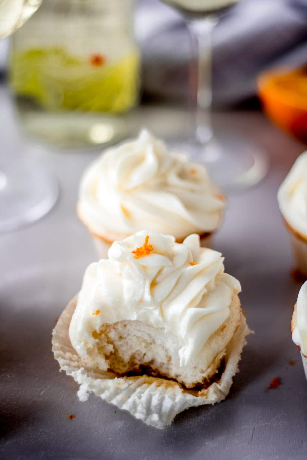an orange moscato cupcake with one bite taken out of it sitting on the table. There's another orange moscato cupcake in the background and a bottle of Moscato