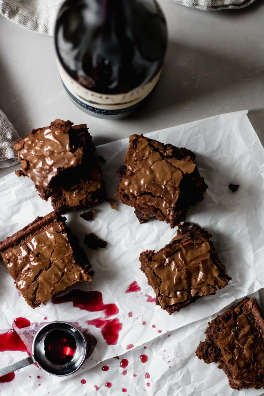 several red wine brownies on a sheet of white parchment paper. there is a measuring spoon with red wine sitting nearby and a bottle of red wine
