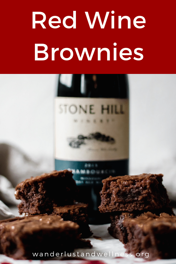 A two-layer stack of brownies with a bottle of red wine in the background