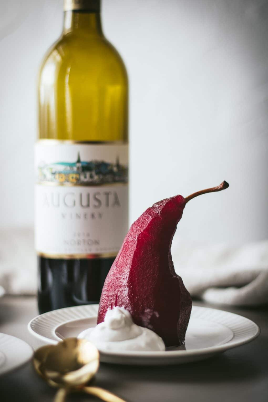 a red wine poached pear on a white plate with a small dollop of coconut cream. There are gold spoons sitting next to the white plate and a bottle of Missouri red wine in the background.