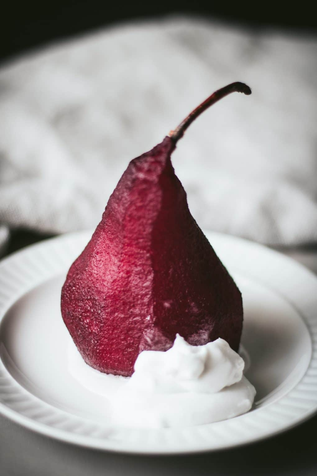 a red wine poached pear sitting on a small white plate with a small dollop of coconut cream.