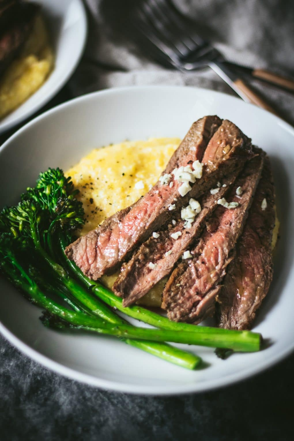 A white bowl with slices of skirt steak sitting on a bed of blue cheese polenta with broccolini on the side