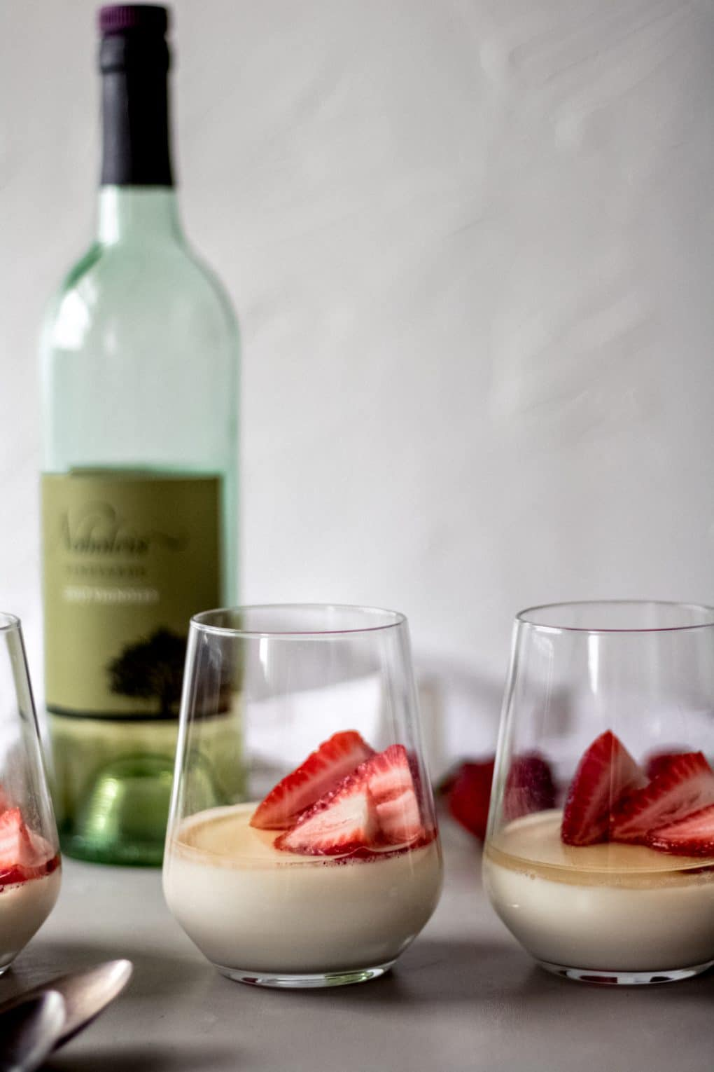 three glasses of vanilla panna cotta with white wine sauce with fresh strawberries in each glass. There's a bottle of white wine in the background and spoons laying in front of the glasses.