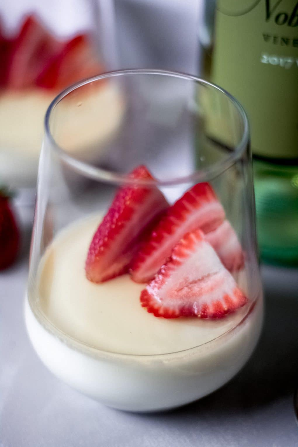 a stemless wine glass with vanilla panna cotta with white wine sauce and fresh strawberries.