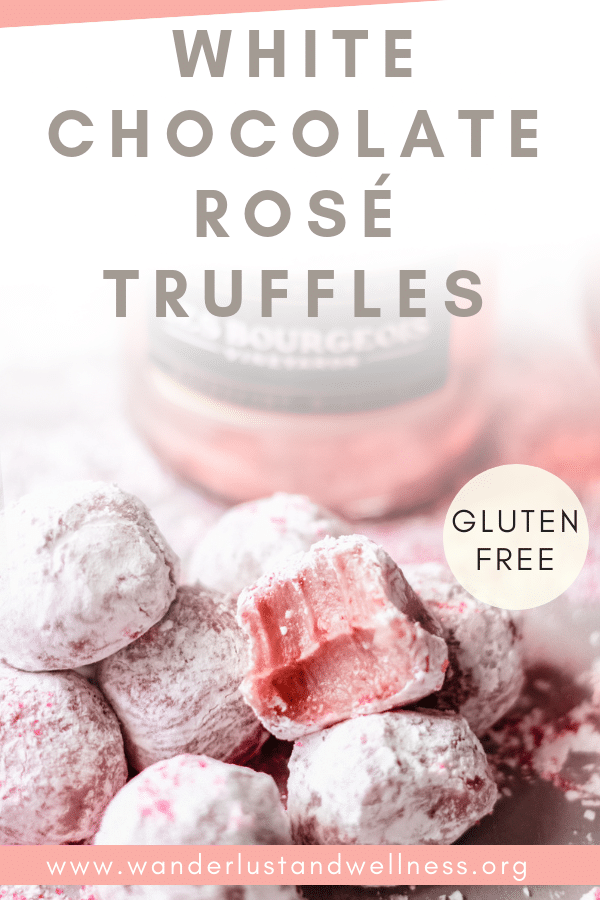 a pile of white chocolate rosé truffles on a table, there is one with a bite taken out of it and a bottle of rosé in the background
