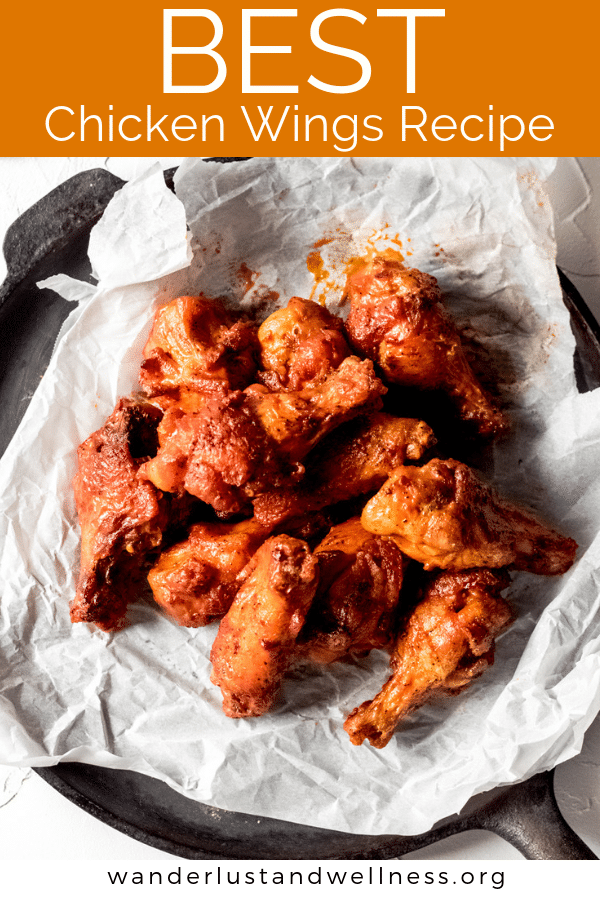 a pile of the best chicken wings recipe wings on a sheet of white parchment paper sitting on a flat cast iron skillet