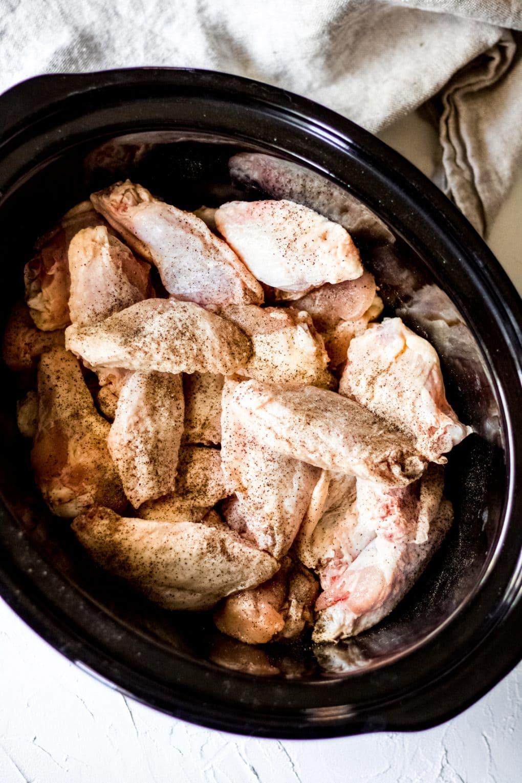 raw chicken wings in a black crock pot