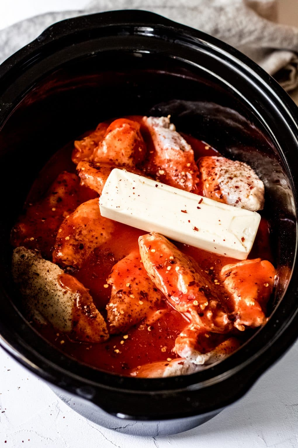raw chicken wings in a crock pot with wing sauce and a stick of butter