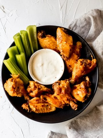 a black bowl with crock pot chicken wings, a bowl of blue cheese dressing, and celery