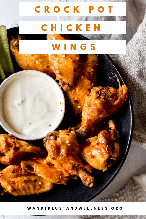 chicken wings in a black bowl with blue cheese in a white dipping bowl.