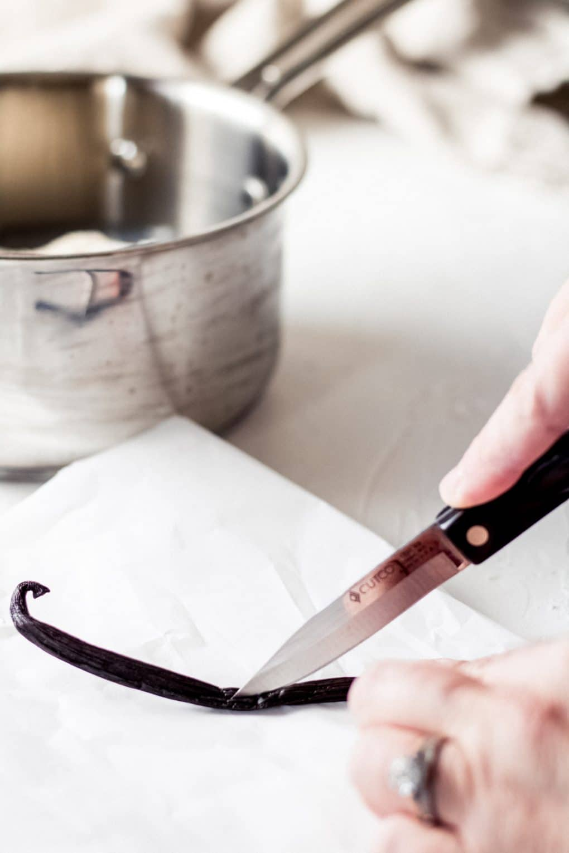 a woman slicing a vanilla bean pod