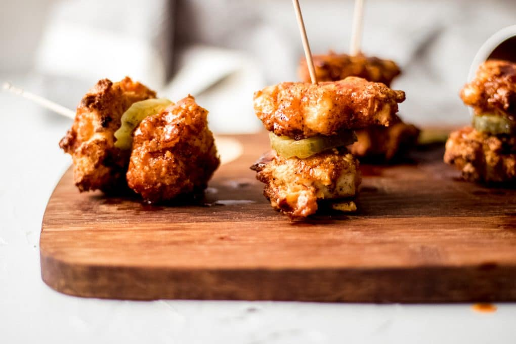 several pieces of gluten-free air fryer nashville hot chicken bites toothpicked together sitting on a wooden cutting board