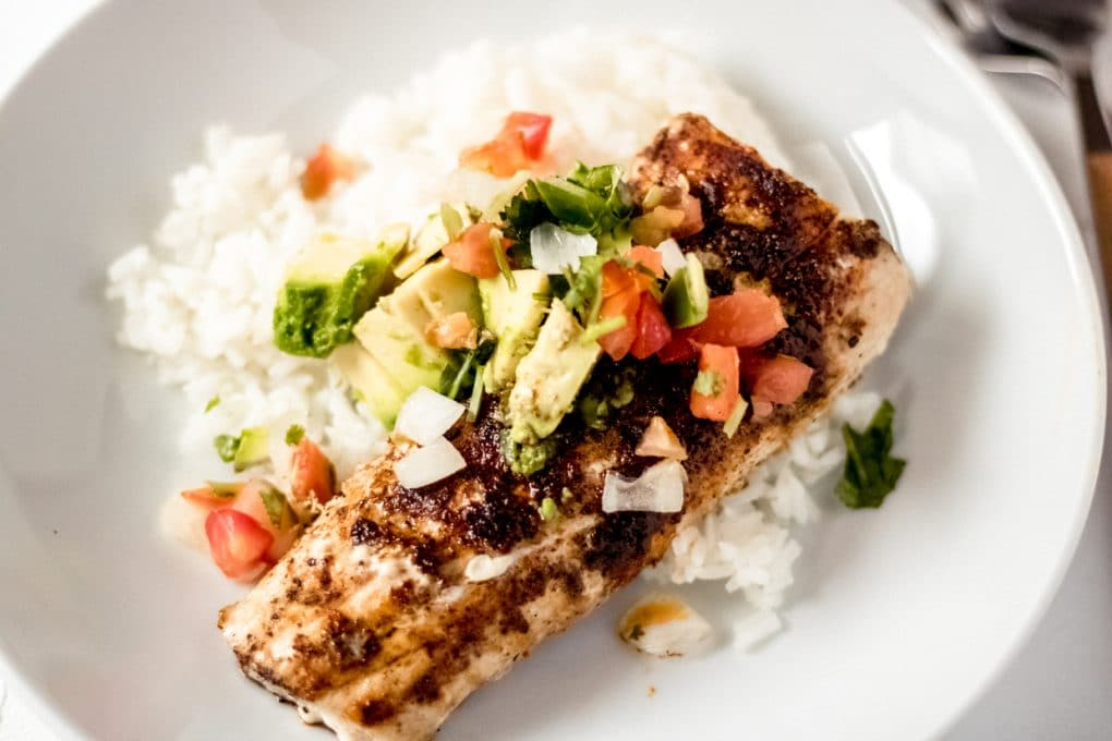 a grilled Mahi Mahi fillet on a bed of white rice in a white bowl topped with pico de gallo and chopped avocado