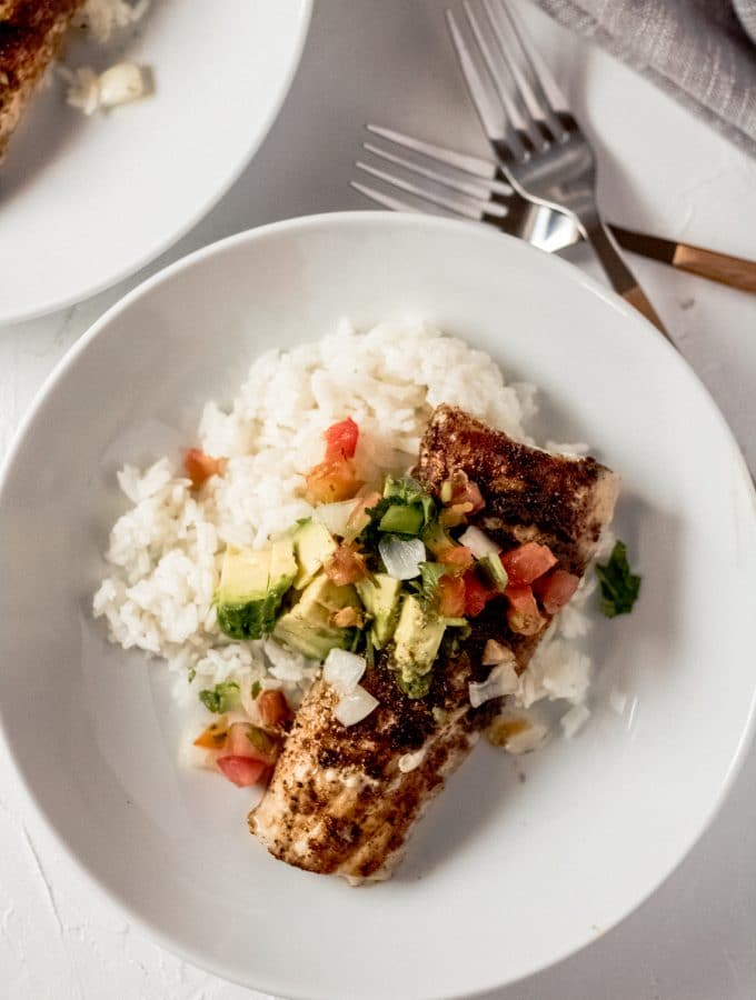 a grilled mahi mahi fillet on a bed of white rice in a white bowl topped with sliced avocado and pico de gallo.