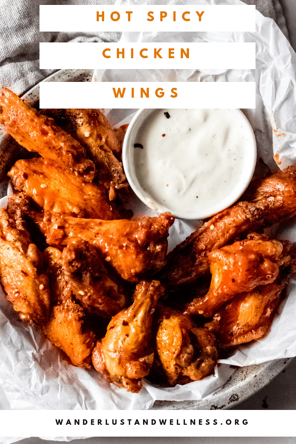 a bowl of hot spicy chicken wings sitting on white parchment paper and a bowl of blue cheese sauce