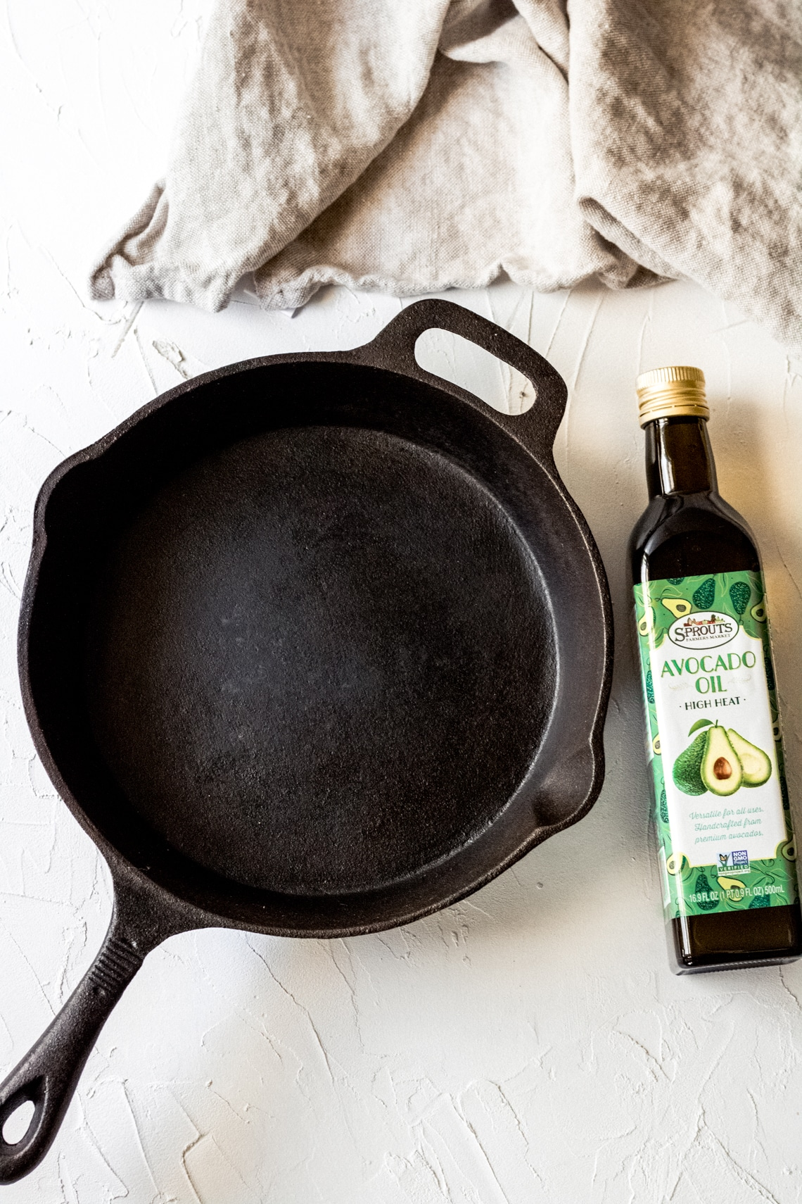 a cast iron skillet and bottle of avocado oil