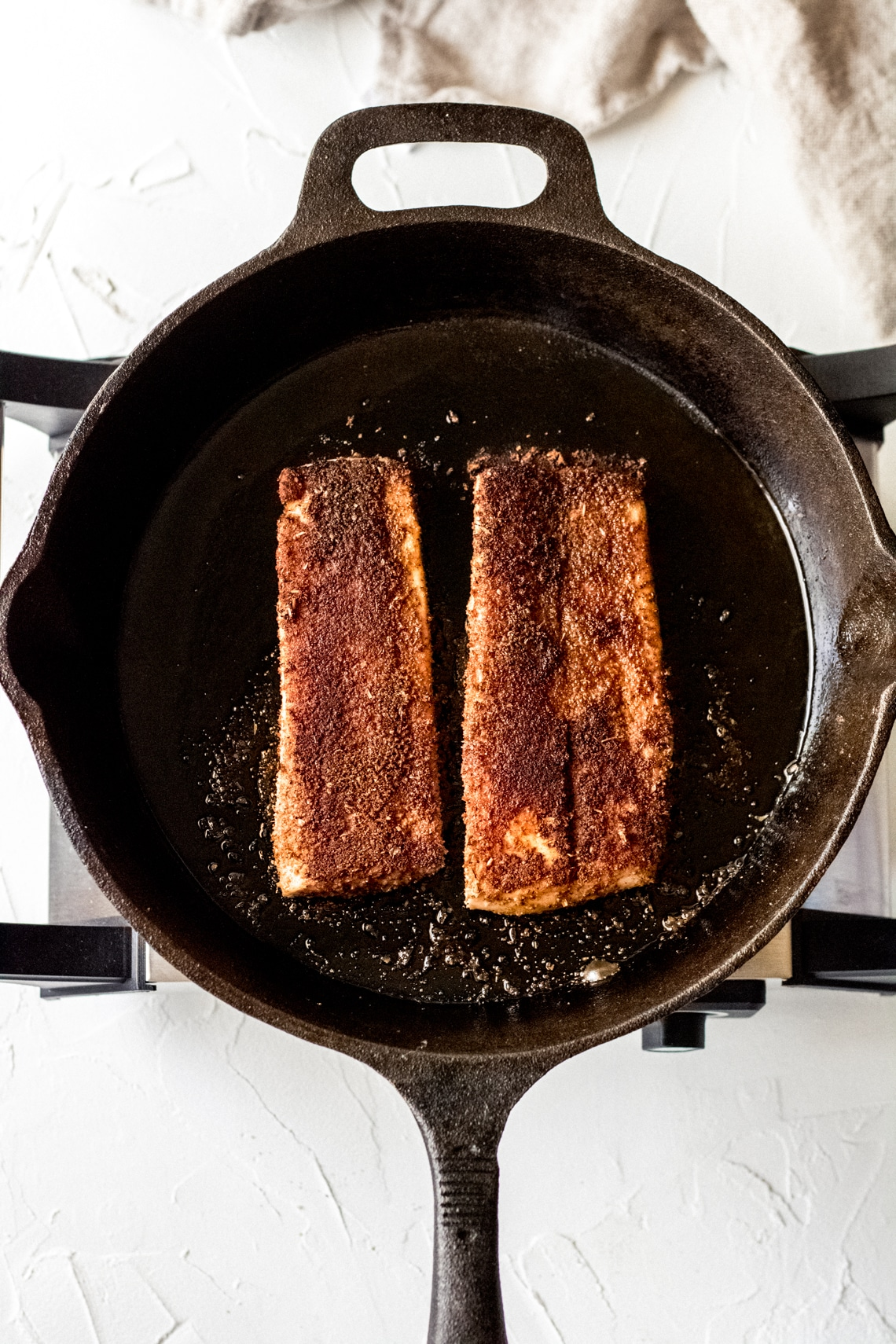 two Mahi mahi fillets cooking in a cast iron skillet
