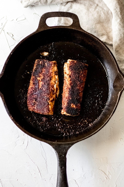 blackened mahi mahi fillets in a cast iron skillet