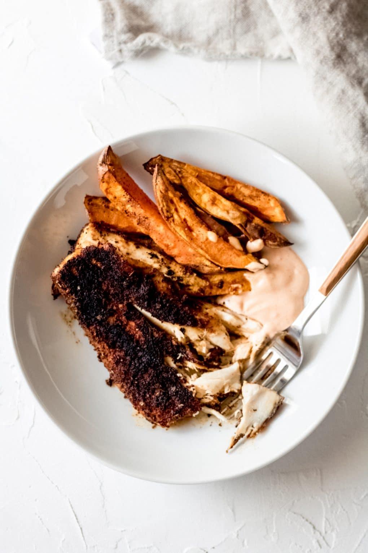 blackened mahi mahi with sweet potato fries and a dipping sauce in a white bowl